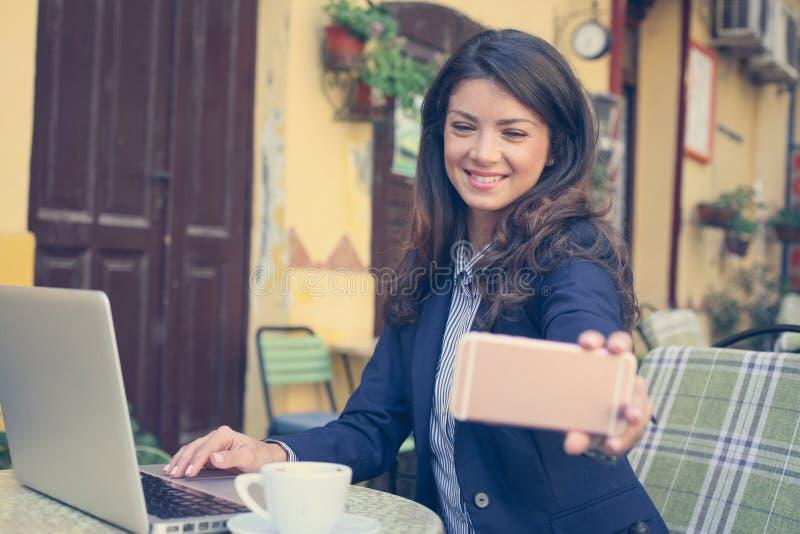 Bedrijfsvrouw die slimme telefoon met behulp van om een zelfportret te nemen royalty-vrije stock foto's