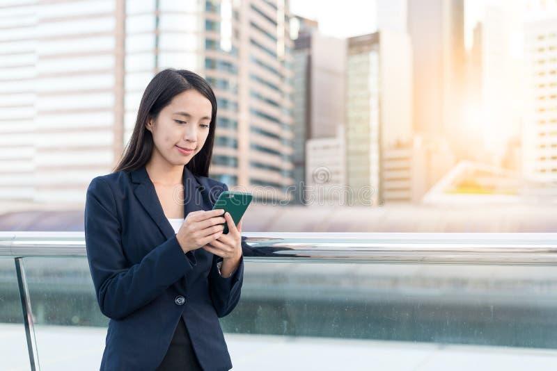 Bedrijfsvrouw die sms op mobiele telefoon in stad verzenden stock afbeelding