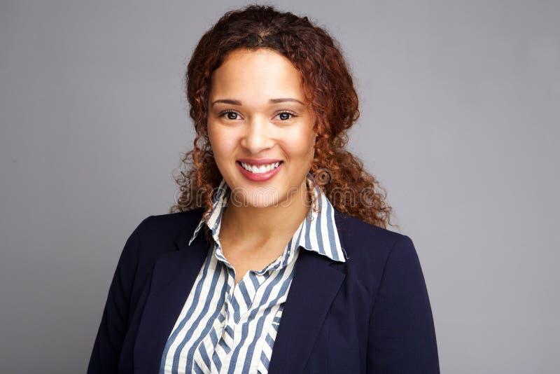 Bedrijfsvrouw die tegen grijze achtergrond glimlachen royalty-vrije stock fotografie