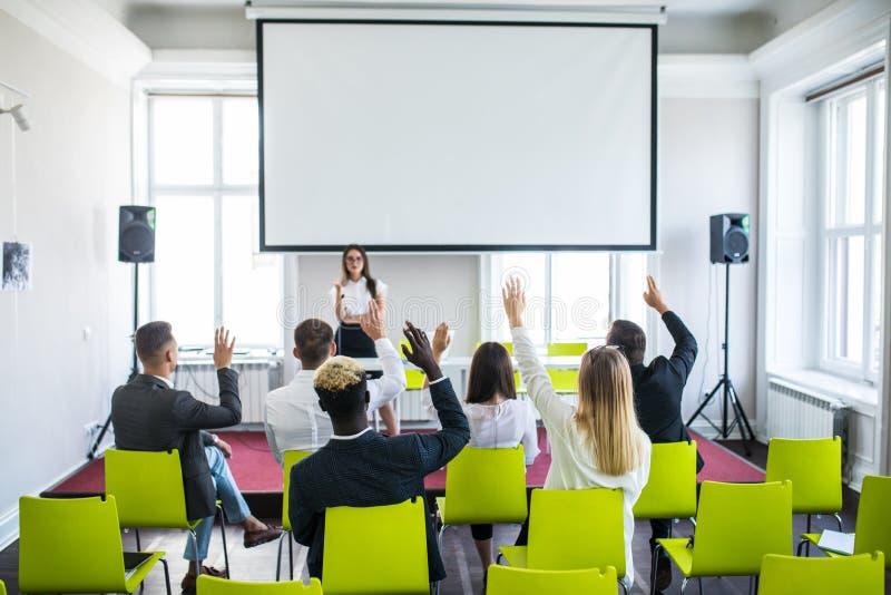 Bedrijfsvrouw die tijdens onderwijsteamvergadering of collectieve opleiding met vrouwenspreker of bus antwoorden royalty-vrije stock foto