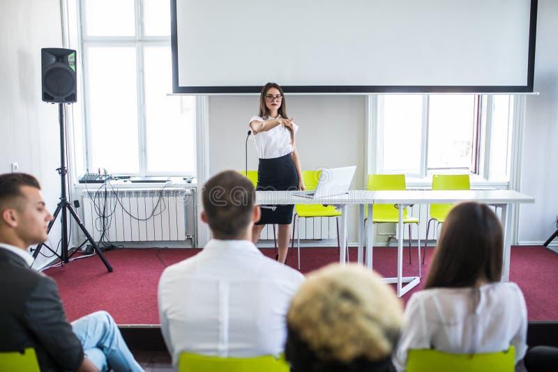 Bedrijfsvrouw die tijdens onderwijsteamvergadering of collectieve opleiding met vrouwenspreker of bus antwoorden stock foto