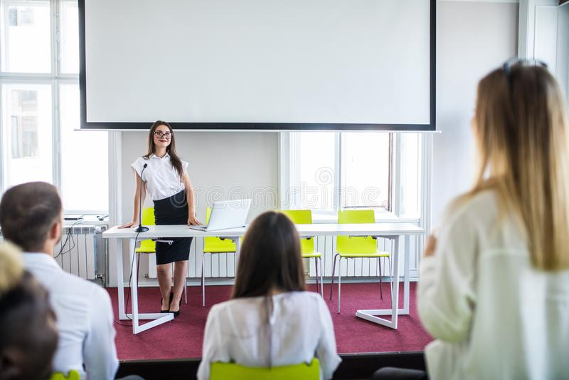 Bedrijfsvrouw die tijdens onderwijsteamvergadering of collectieve opleiding met vrouwenspreker of bus antwoorden stock fotografie
