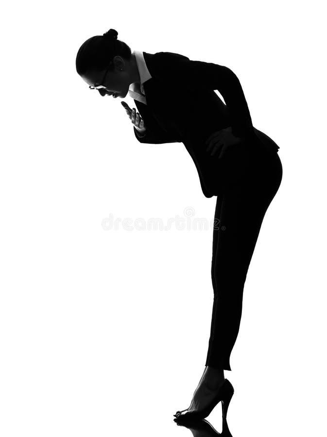 Bedrijfsvrouw die verrast silhouet buigen stock foto's