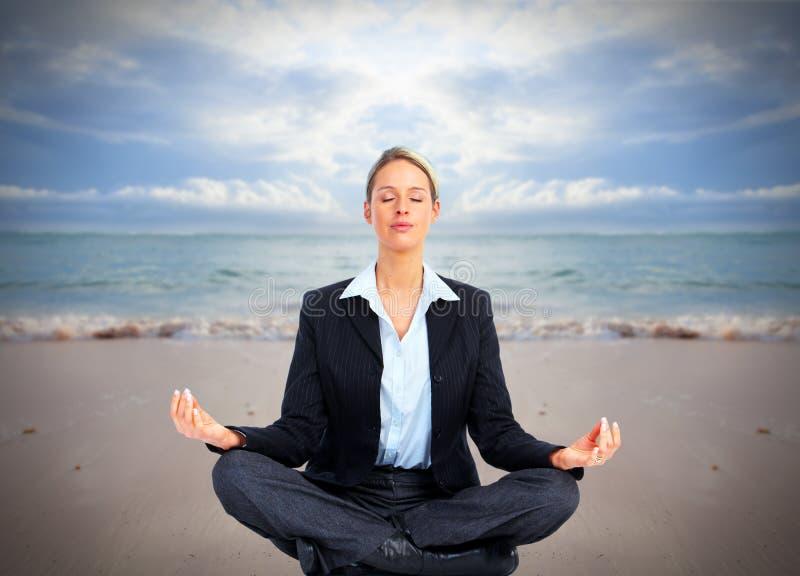 Bedrijfsvrouw die yoga op het strand doen. stock fotografie