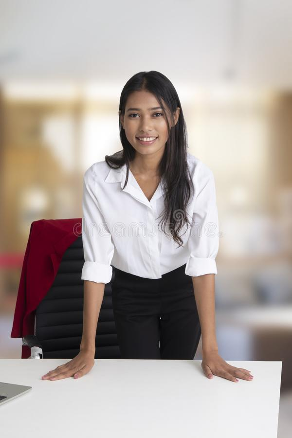Bedrijfsvrouw die zich achter het bureau met vriendschappelijke glimlach bevinden royalty-vrije stock afbeeldingen