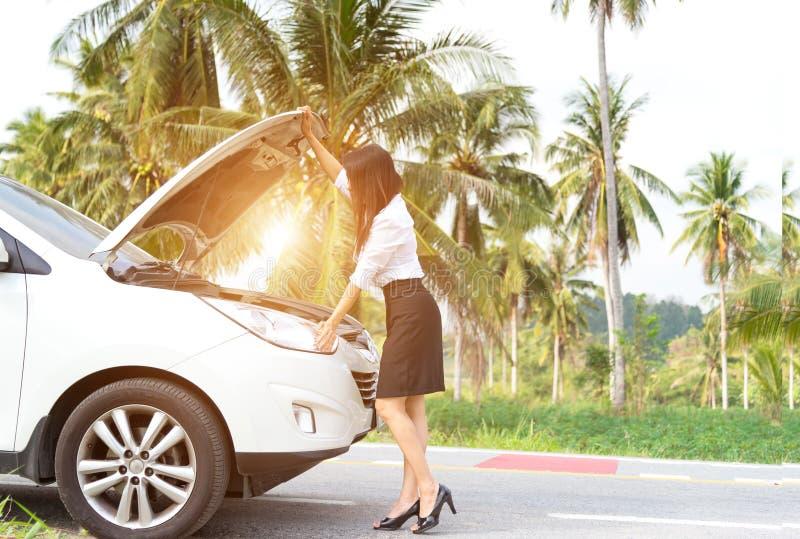 Bedrijfsvrouw die zich door gebroken auto bevinden royalty-vrije stock fotografie