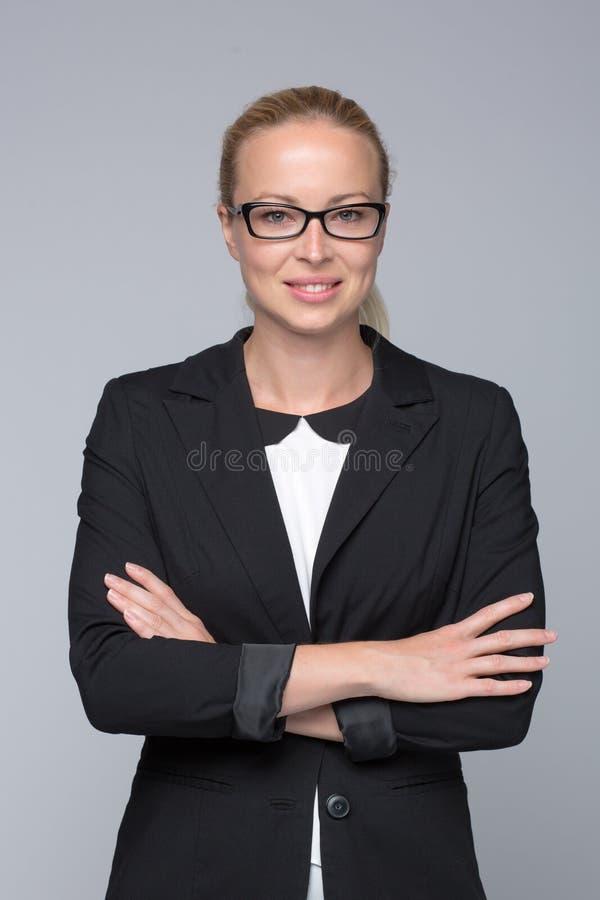 Bedrijfsvrouw die zich met die wapens bevinden tegen grijze achtergrond worden gekruist stock afbeeldingen