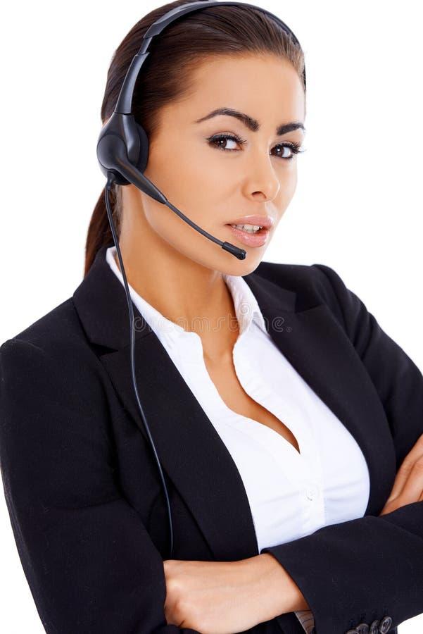 Bedrijfsvrouw die zich met gekruiste wapens bevinden, dragend hoofdtelefoon royalty-vrije stock afbeeldingen