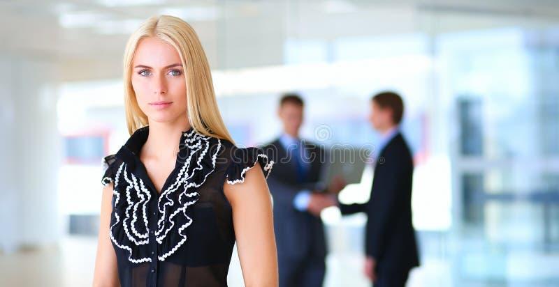 Download Bedrijfsvrouw Die Zich In Voorgrond In Bureau Bevinden Stock Foto - Afbeelding bestaande uit carrière, emotie: 107704364