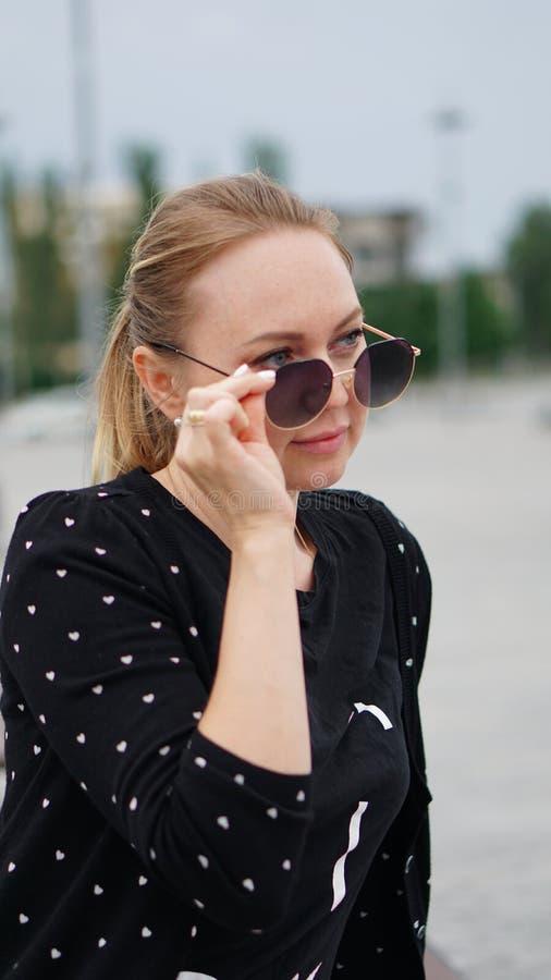 Bedrijfsvrouw die in zwart jasje van zonnebril kijken stock fotografie