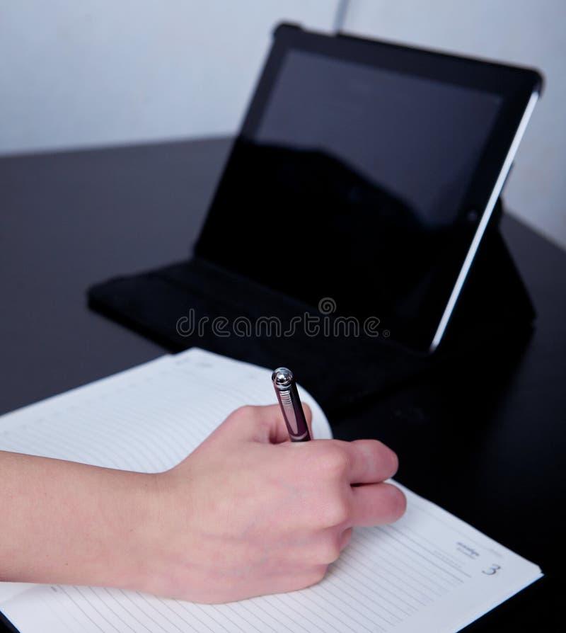Bedrijfsvrouw in een koffie die nota's in een agenda maken royalty-vrije stock afbeeldingen