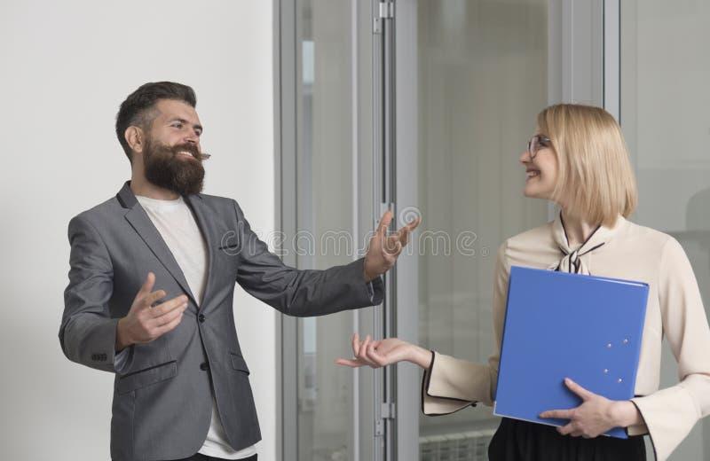 Bedrijfsvrouw en man collega's in bureau Gebaarde man bespreking aan sensuele vrouw met bindmiddel De beambten dragen formeel stock fotografie