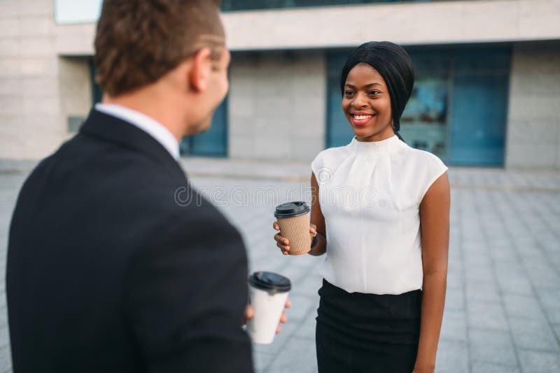 Bedrijfsvrouw en zakenman met koffiekoppen stock afbeeldingen
