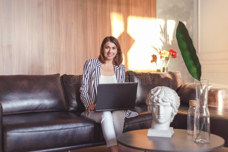 Bedrijfsvrouw in jasje op leerbank die in creatief kunstbureau werken stock afbeeldingen