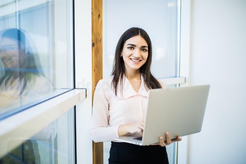 Bedrijfsvrouw in kledingszitting dichtbij het venster en het gebruiken van laptop in bureau stock fotografie