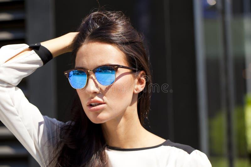 Bedrijfsvrouw met blauwe weerspiegelde zonnebril stock afbeeldingen