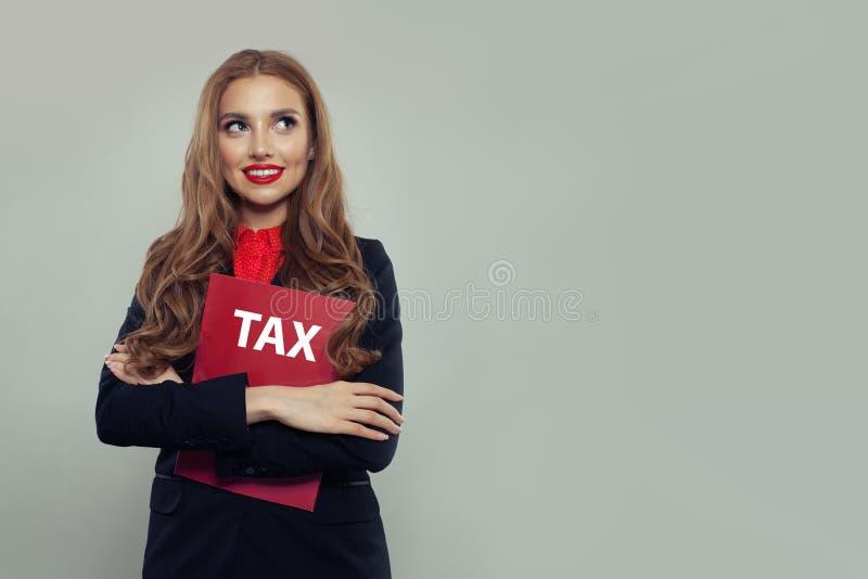 Bedrijfsvrouw met rood belastingenrapport over grijze bannerachtergrond Onderneemster in zwart kostuumportret stock foto