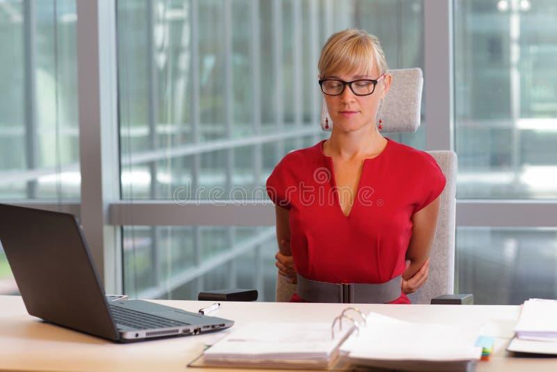 bedrijfsvrouw in oogglazen ontspannen, die zich terug uitrekken stock foto