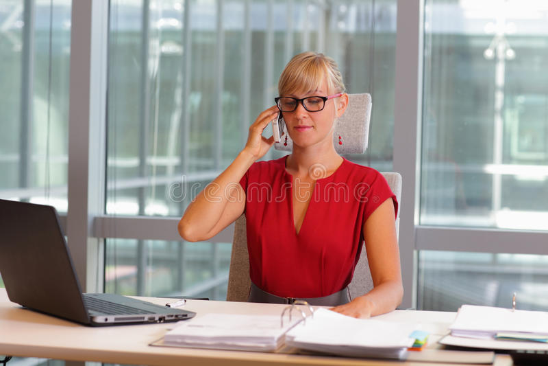 Bedrijfsvrouw in oogglazen op telefoon in haar bureau royalty-vrije stock foto