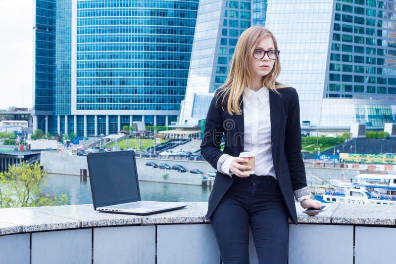 Bedrijfsvrouw op koffiepauze met een laptop zitting op de straat royalty-vrije stock afbeeldingen