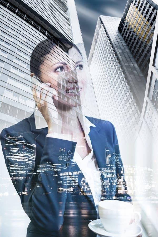Bedrijfsvrouw op telefoon, de achtergrond van de financiënarchitectuur, dubbel stock afbeeldingen