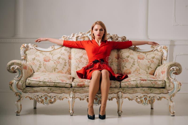 Bedrijfsvrouw in rode kleding op luxebank bedrijfsdame die op vergadering wachten de bedrijfsvrouw ontspant na werkdag royalty-vrije stock foto