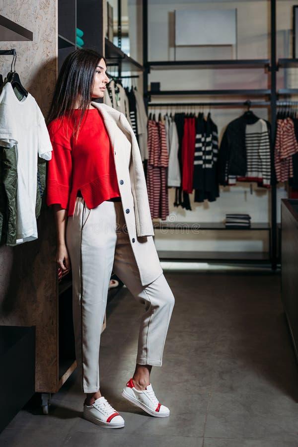 Bedrijfsvrouw in rode sweater en laag in kledingsopslag stock fotografie