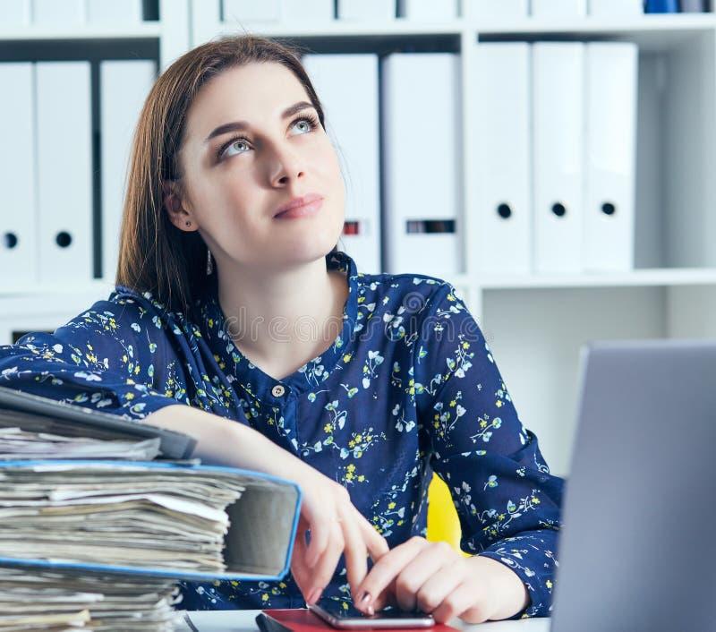 Bedrijfsvrouw of secretaresse met vele rekeningen van documentenomslagen op haar bureau die onderbreking nemen, die bij het werk  stock foto's