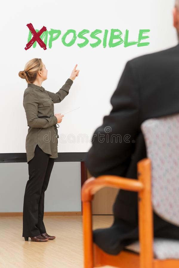 Bedrijfsvrouw voor een canvas met het woord mogelijke stock foto
