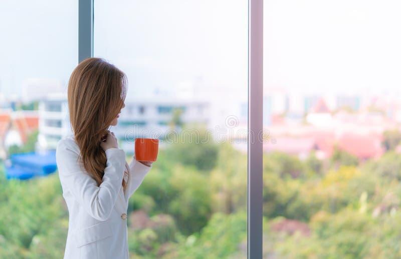 Bedrijfsvrouw in wit die een rode koffiekop houden door de vensters stock afbeelding