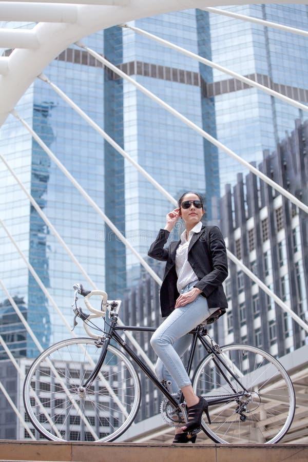 Bedrijfsvrouwen berijdende fiets om aan stedelijke straat in stad te werken vervoer en gezond koele slim van de manierlevensstijl royalty-vrije stock fotografie