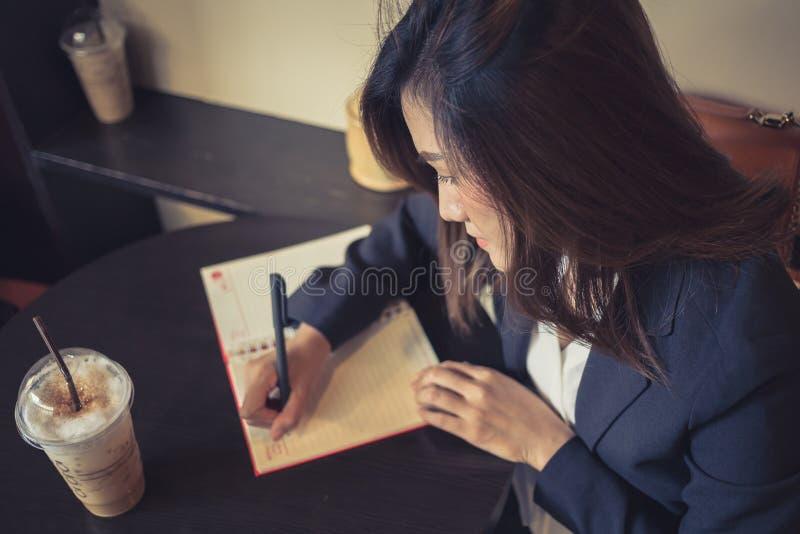 Bedrijfsvrouwen die het schrijven in de koffie werken stock foto