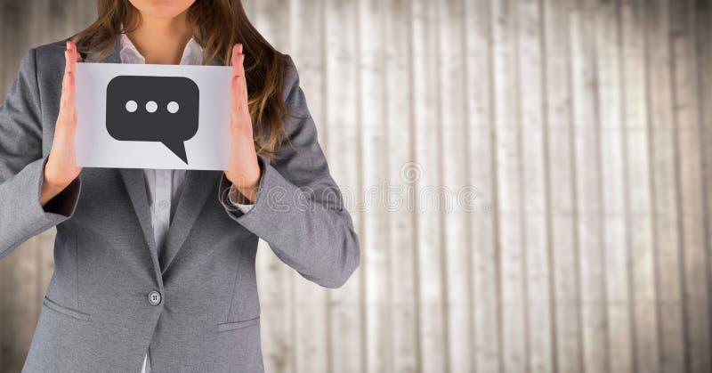 Bedrijfsvrouwen medio sectie met kaart die toespraakbel grafisch tegen onscherp houten paneel tonen royalty-vrije stock foto's