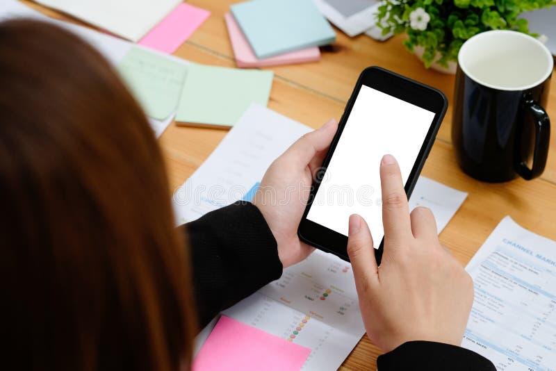 Bedrijfsvrouwenaanraking op spot op smartphone op bureauwerkplaats stock fotografie