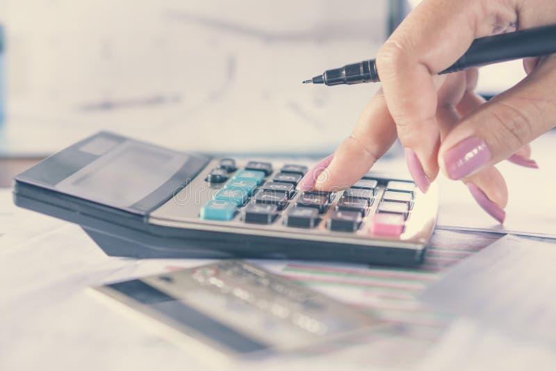 Bedrijfsvrouwenhand die haar maandelijkse uitgaven met creditcard, idee voor online het winkelen berekenen royalty-vrije stock afbeelding