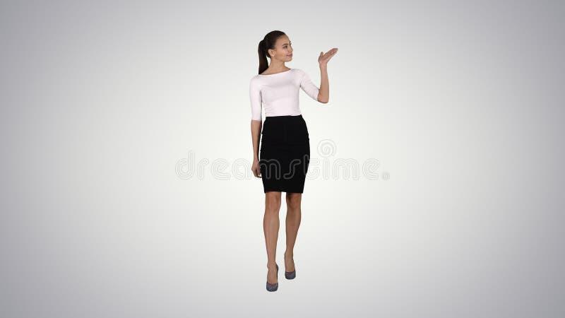 Bedrijfsvrouwenpresentator die en product of tekst op gradiëntachtergrond spreken tonen royalty-vrije stock foto