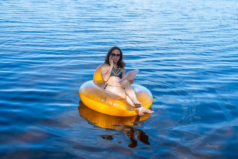 Bedrijfsvrouwenwerkverslaafde het werk zitting in een opblaasbare ring op het overzees tijdens de vakantie, vrije ruimte royalty-vrije stock fotografie