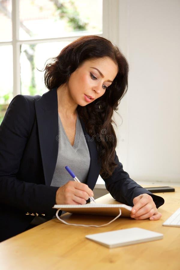 Bedrijfsvrouwenzitting bij bureau het schrijven nota's in boek stock foto