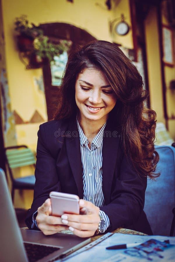 Bedrijfsvrouwenzitting bij koffie die slimme telefoon met behulp van stock fotografie