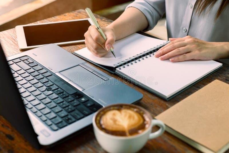 Bedrijfsvrouwenzitting bij lijst en het nemen van nota's in notitieboekje Op royalty-vrije stock afbeeldingen