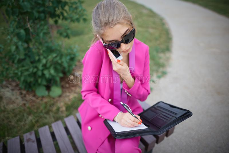 Bedrijfsvrouwenzitting op een bank in de straat royalty-vrije stock fotografie