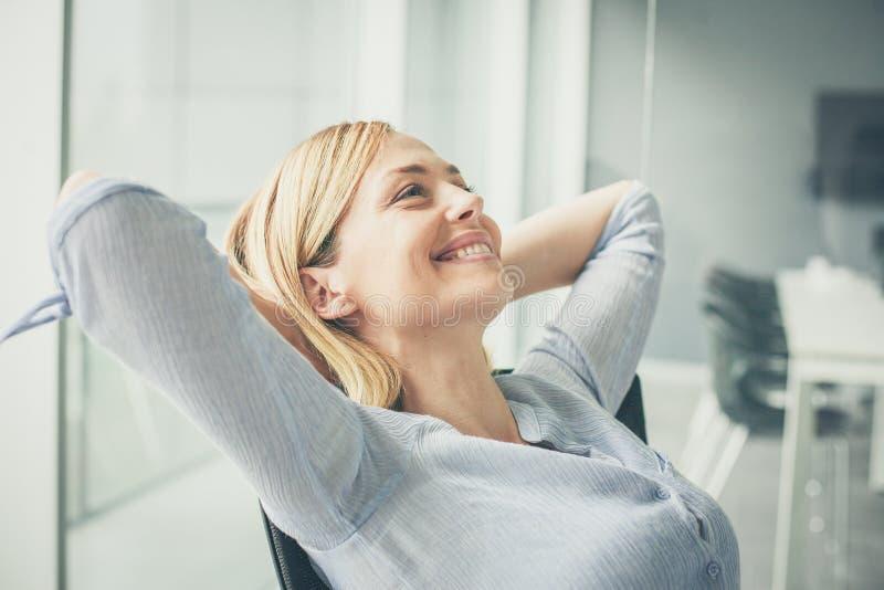 Bedrijfsvrouwenzitting op stoel en het ontspannen stock foto's