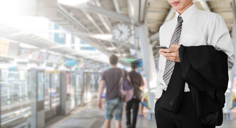 Bedrijfswerknemer die smartphone gebruiken, terwijl het wachten op BTS-hemeltrein aan gaand bureau voor het werken in spitsuuroch royalty-vrije stock afbeeldingen