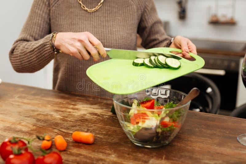 Bedrijvige nauwkeurige vrouw die gehakte komkommers toevoegen in glaskom royalty-vrije stock afbeeldingen