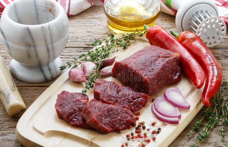 bedroll Свежее сырое мясо на разделочной доске, оливковом масле, чесноке, горячем перце, тимиане и специях стоковые фото