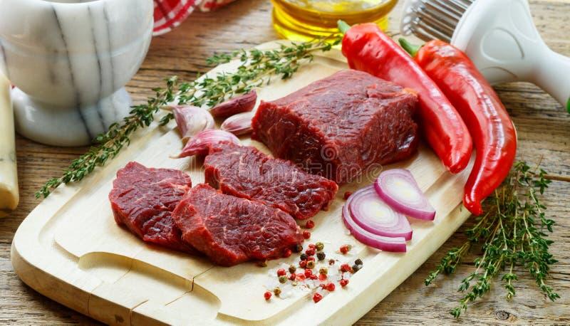 bedroll Свежее сырое мясо на разделочной доске, оливковом масле, чесноке, горячем перце, тимиане и специях стоковые фотографии rf