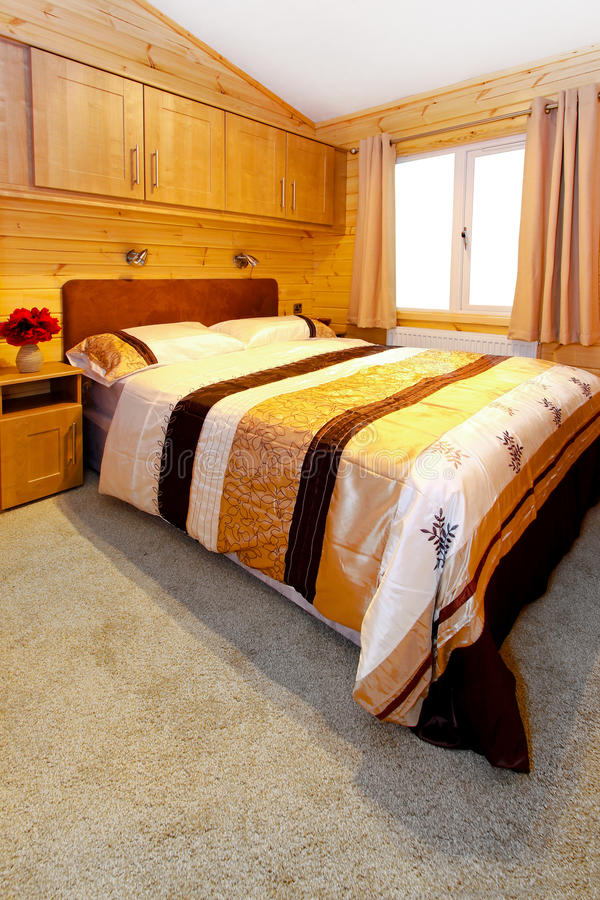Bedroom. Wooden bedroom interior in mountain cabin house royalty free stock photo