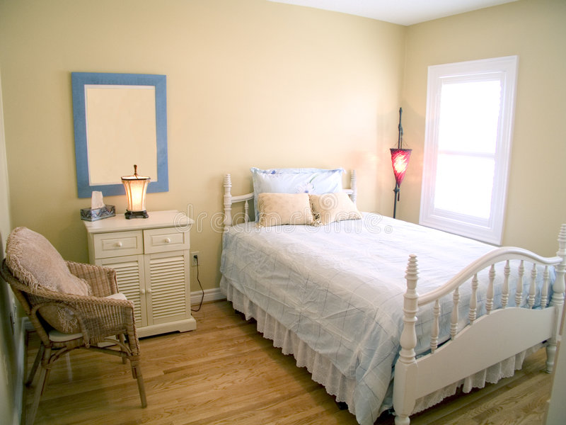 Bedroom 49. Bedroom with wood floor, white ceiling, window, red lamp, bedside table and throw pillows