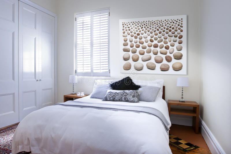 Bedroom Bed Art. A bedroom with window light coming through the shutters. With pillows and bedside tables and art royalty free stock photography