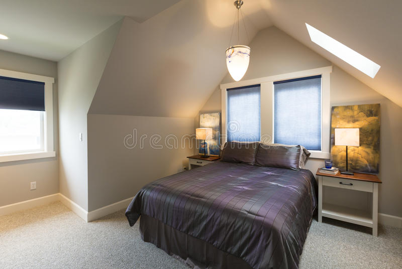Bedroom with bed, bedside tables, vaulted ceiling, window coverings and accent lighting in contemporary upscale home interior. Bedroom with bed, bedside tables stock images